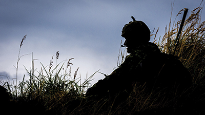 Soldier on guard in a field.