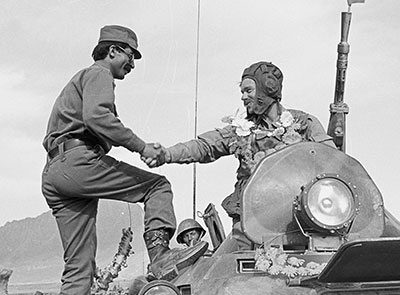A garlanded Russian soldier shakes hands with an Afghan soldier who climbed up on the tank to welcome more than 1000 Soviet troops returning from the eastern city of Jalalabad as part of the troop withdrawal, which began on 15 May 1988.